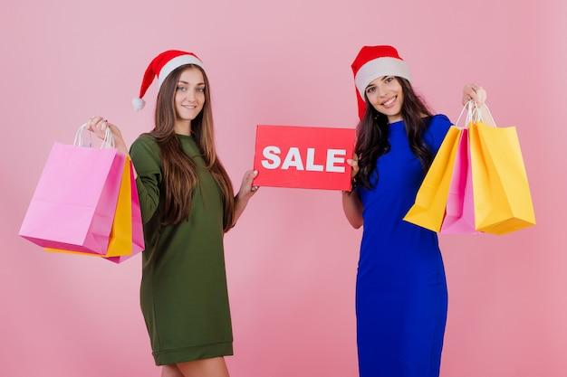 Zwei frauen, die sankt-hüte mit den bunten feiertagseinkaufstaschen und copyspace verkauf tragen, unterzeichnen getrennt über rosa Premium Fotos