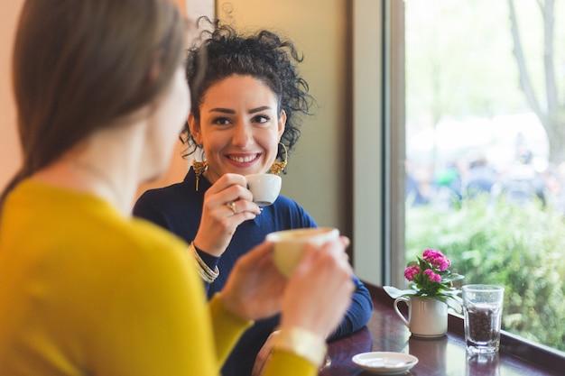 Zwei frauen in einem café, das zusammen kaffee lächelt und trinkt Premium Fotos
