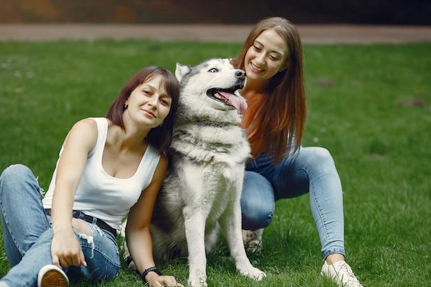 Zwei frauen in einem frühlingspark, der mit nettem hund spielt Kostenlose Fotos