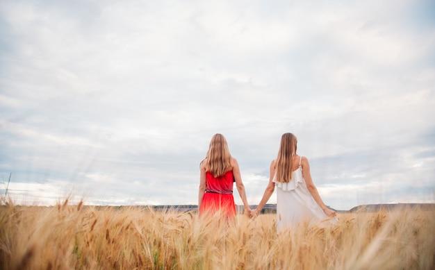 Zwei frauen in kleidern auf einem weizenfeld Premium Fotos