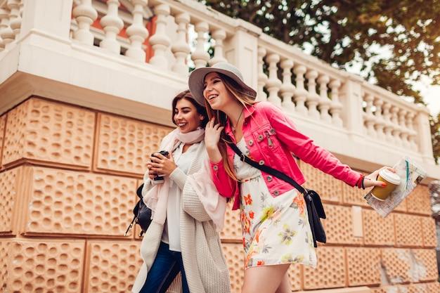 Zwei frauentouristen, die den spaß haben, unter verwendung der karte in odessa besichtigt zu werden. glückliche lachende freundreisende beim gehen Premium Fotos