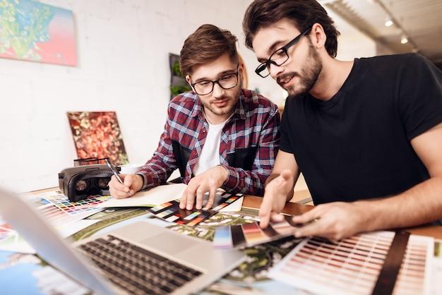 Zwei freiberuflermänner, die farbmuster auf laptop betrachten. Premium Fotos