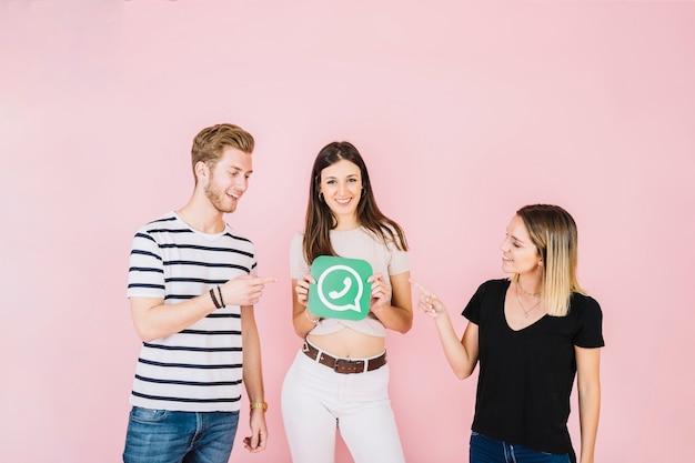 Zwei freunde, die auf die lächelnde frau whatsapp ikone halten zeigen Kostenlose Fotos