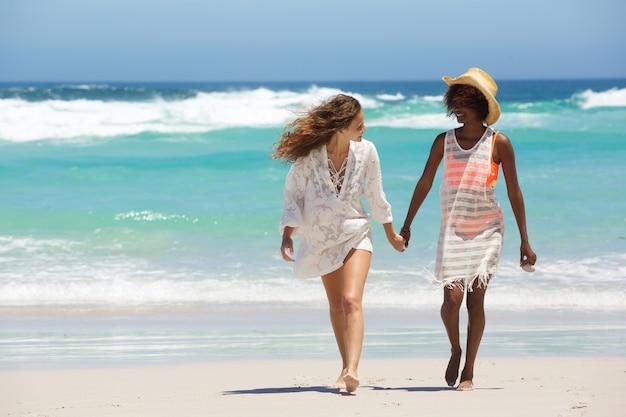 Zwei freunde, die zusammen am strand gehen Premium Fotos