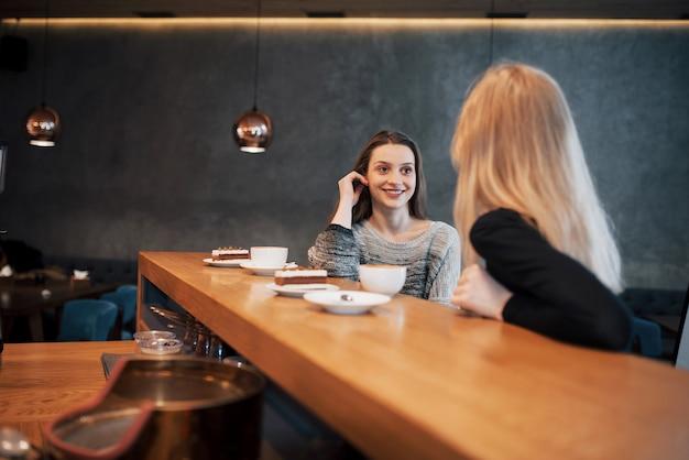 Zwei freunde genießen gemeinsam kaffee in einem café, während sie an einem tisch sitzen und sich unterhalten Premium Fotos
