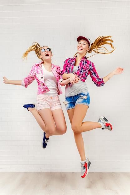 Zwei freunde posieren und springen Premium Fotos