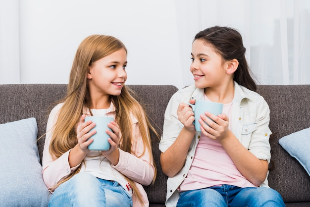 Zwei freundinnen, die auf dem sofa in der hand hält kaffeetasse einander betrachtend sitzen Kostenlose Fotos