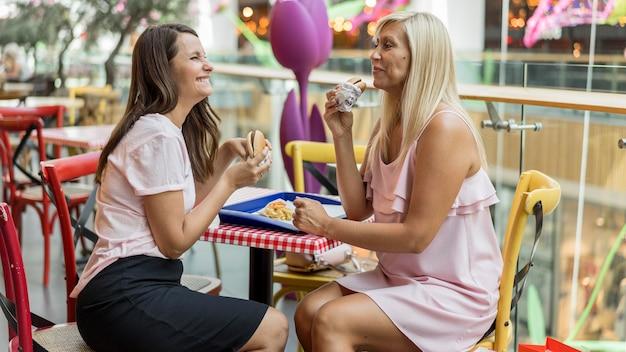 Zwei freundinnen, die burger zusammen im restaurant genießen Kostenlose Fotos