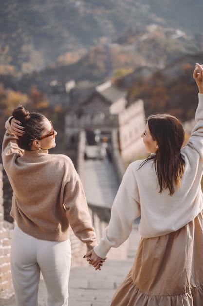 Zwei freundinnen, die entlang die chinesische mauer nahe dem peking entarnce gehen Kostenlose Fotos