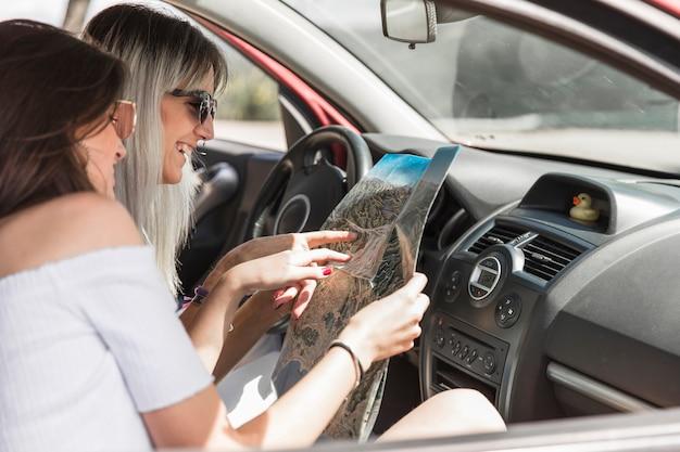 Zwei freundinnen, die im auto sucht richtungen auf karte sitzen Kostenlose Fotos
