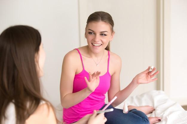 Zwei freundinnen, die neue kosmetik teilen und ausprobieren Kostenlose Fotos