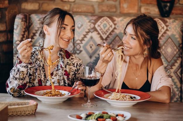 Zwei freundinnen, die nudeln in einem italienischen restaurant essen Kostenlose Fotos