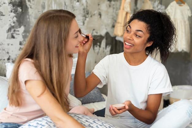 Zwei freundinnen helfen sich gegenseitig beim schminken Kostenlose Fotos