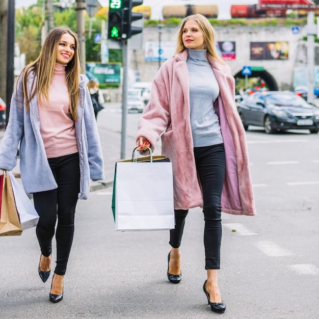 Zwei freundinnen im stilvollen pelzmantel gehend auf die straße, die einkaufstaschen hält Kostenlose Fotos