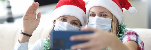 Zwei freundinnen in schützenden gesichtsmasken und roten weihnachtsmützen werden auf telefonporträt fotografiert Premium Fotos