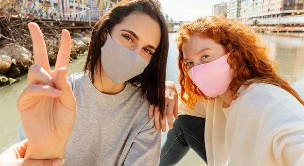Zwei freundinnen mit gesichtsmasken im freien nehmen ein selfie zusammen Kostenlose Fotos