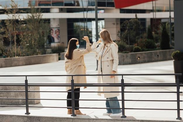Zwei freundinnen mit schutzgesichtsmasken grüßen, indem sie ellbogen stoßen. begrüßung des ellenbogens, um die ausbreitung des coronavirus zu vermeiden. Premium Fotos