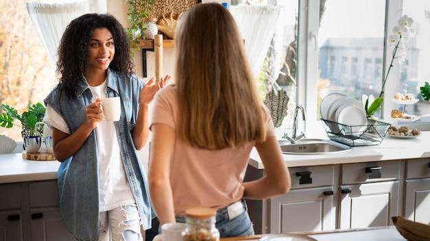 Zwei freundinnen unterhalten sich in der küche Kostenlose Fotos