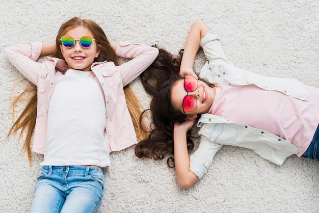 Zwei freundinnen, welche die stilvolle sonnenbrille liegen auf weißem teppich tragen Kostenlose Fotos
