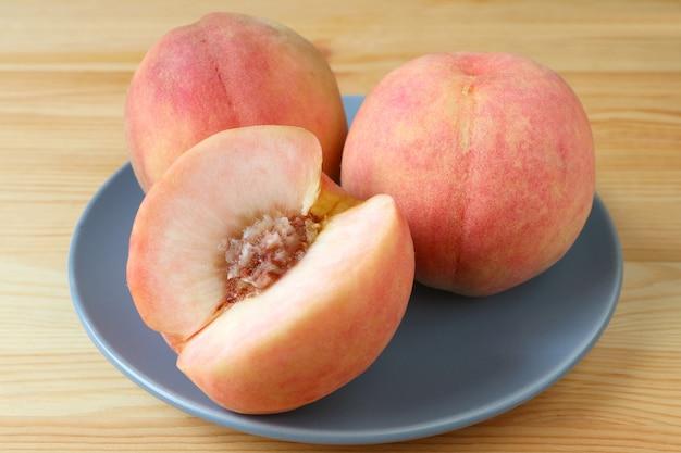 Zwei frische reife pfirsich-ganze früchte und ein geschnittener pfirsich auf einer blauen platte gedient auf holztisch. Premium Fotos