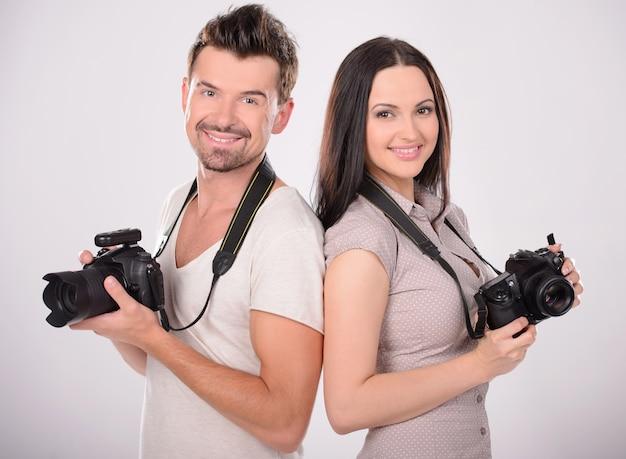 Zwei fröhliche fotografen halten kameras. Premium Fotos