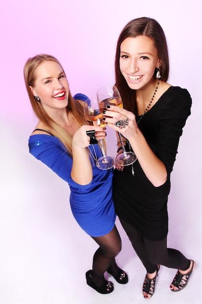 Zwei fröhliche freundinnen mit bunten cocktails Kostenlose Fotos