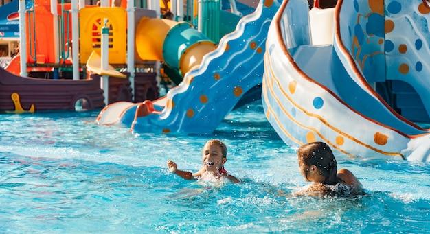 Zwei fröhliche glückliche mädchenschwestern, die spaß haben und in einem pool mit klarem klarem wasser in einem lang erwarteten erholsamen urlaub lachen Premium Fotos
