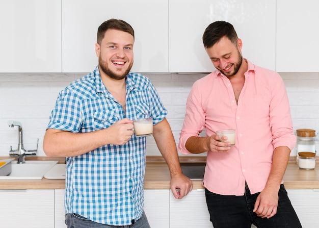 Zwei fröhliche junge männer mit kaffee in der küche