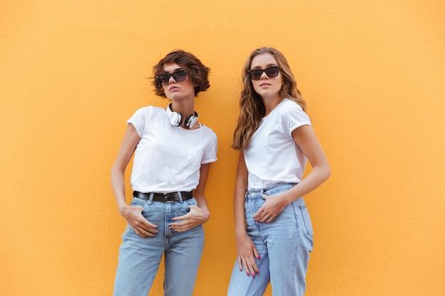 Zwei fröhliche junge teenager-mädchen in der sonnenbrille posiert Kostenlose Fotos