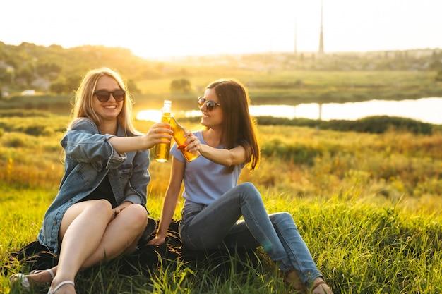 Zwei fröhliche mädchen und junge freunde mit sonnenbrille, bier trinken und gemeinsam die zeit bei sonnenuntergang genießen. Premium Fotos