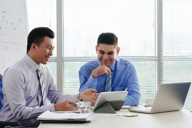 Zwei fröhliche manager, die beim brainstorming ideen generieren Kostenlose Fotos