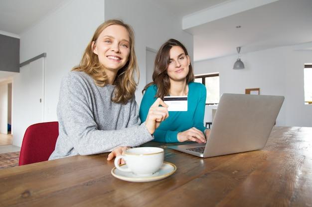 Zwei fröhliche weibliche kunden, die online zahlen Kostenlose Fotos