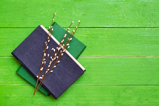 Zwei gebundene bücher auf einem grünen holz und weidenzweigen. ansicht von oben Premium Fotos