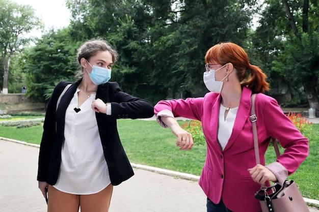 Zwei geschäftsfrau mit gesichtsmaske während der begrüßungsbögen Premium Fotos
