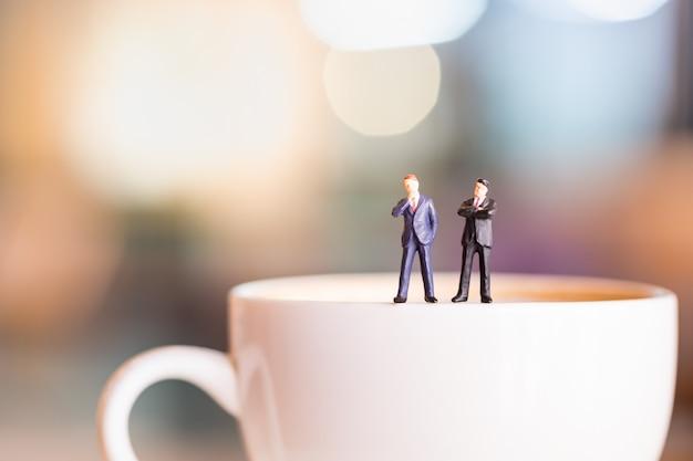 Zwei geschäftsmannminiaturzahlen stehen und denken auf weißer platte der schale heißen kaffees. Premium Fotos