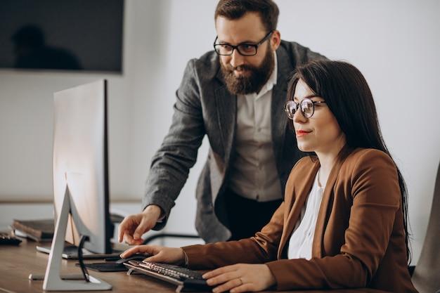 Zwei geschäftspartner arbeiten im büro am computer zusammen Kostenlose Fotos