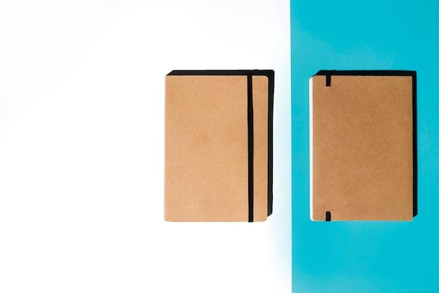 Zwei geschlossenes notizbuch mit brauner abdeckung auf weißem und blauem hintergrund Kostenlose Fotos