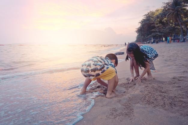 Zwei geschwisterkinder spielen mit welle und sand in pattaya-strand thailand Premium Fotos