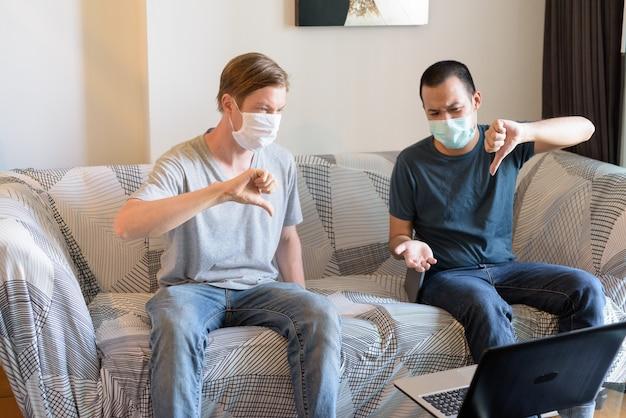 Zwei gestresste multiethnische männer mit maske als freunde, die beim videoanruf in der quarantäne zu hause daumen runter geben Premium Fotos