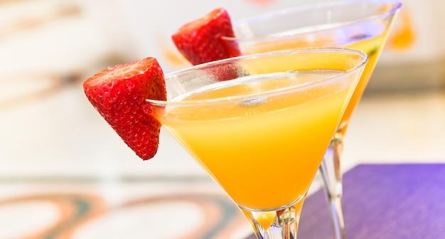 Zwei gläser bellini-cocktail mit prosecco, erdbeer-dekor, italienische bar Premium Fotos
