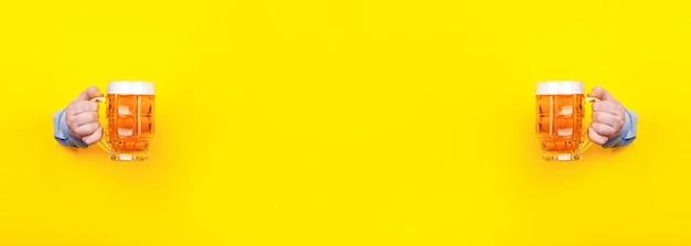 Zwei gläser bier in den händen auf einem gelben Premium Fotos
