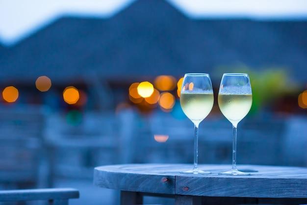 Zwei gläser geschmackvoller weißer wein am sonnenuntergang Premium Fotos