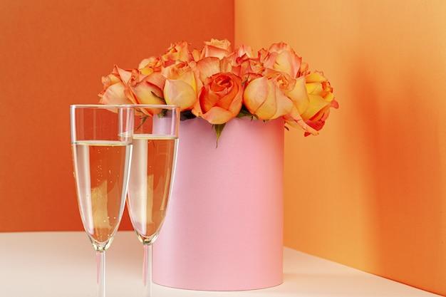 Zwei gläser mit champagner und einem strauß rosen Premium Fotos