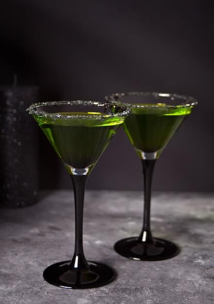 Zwei gläser mit grünem zombiecocktail für halloween-partei auf dem grauen hintergrund Premium Fotos