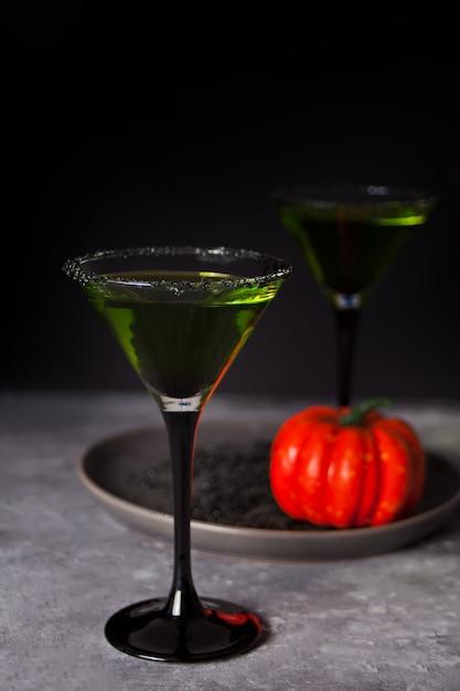 Zwei gläser mit grünem zombiecocktail für halloween-party auf dunkelheit Premium Fotos