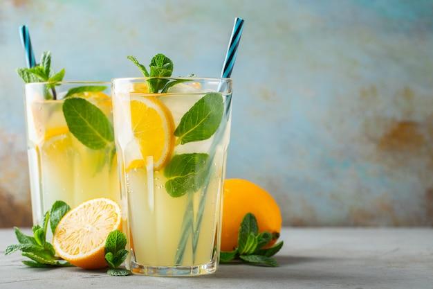 Zwei gläser mit limonade oder mojito-cocktail mit zitrone und minze, kaltem erfrischungsgetränk oder getränk Premium Fotos