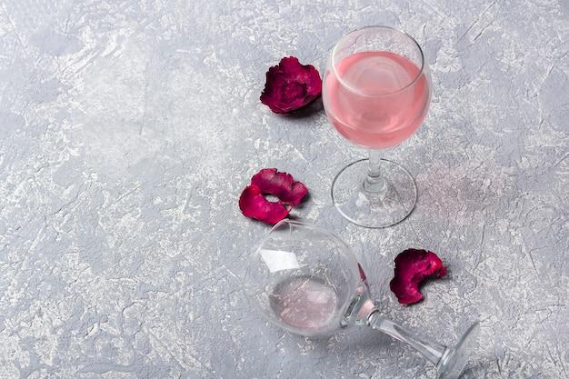 Zwei gläser mit roséwein und roten rosenblättern auf grauem hintergrund. halb leeres glas liegt auf der seite. weinprobe. betrunkenheitskonzept. Premium Fotos
