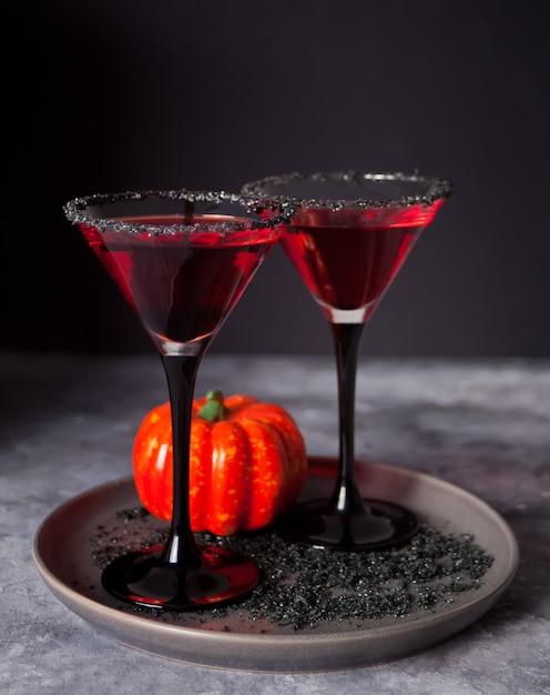 Zwei gläser mit rotem cocktail für halloween-party auf dunkelheit Premium Fotos