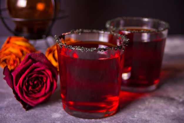 Zwei gläser mit rotem cocktail, getrocknete rosen für halloween-party auf der dunkelheit Premium Fotos
