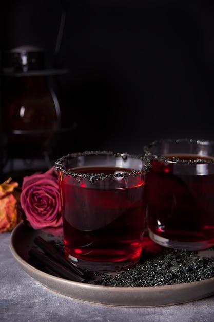 Zwei gläser mit rotem cocktail, getrocknete rosen für halloween-party auf dunkelheit Premium Fotos
